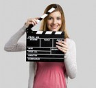 Beautiful blonde woman holding  a clapboard, isolated over gray background