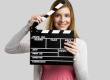 Beautiful girl holding clapboard