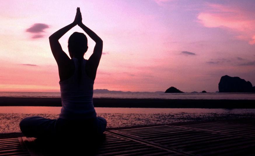 Photo coucher de soleil, femme méditant le regard tourné vers l'horizon