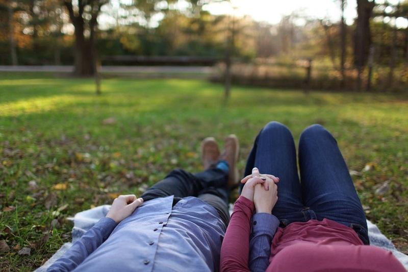 couple-sortie-au-parc-en-amoureux-allonges-tous-les-deux