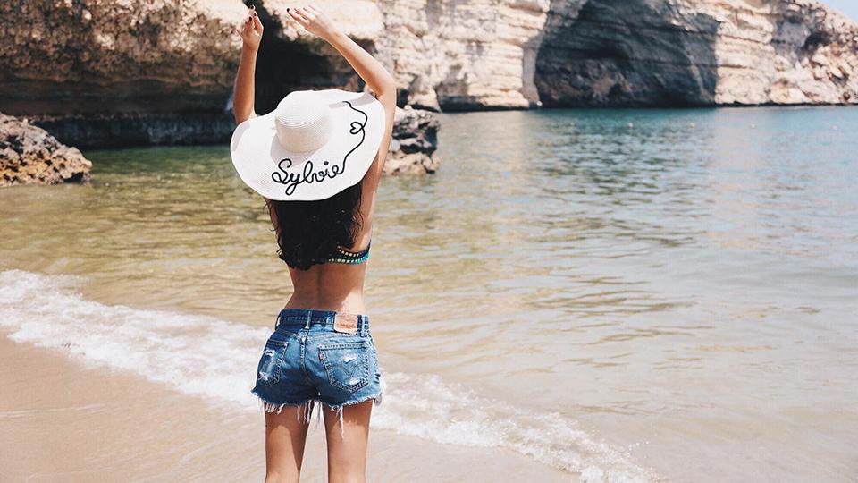 femme-en-maillot-de-bain-et-short-a-la-plage