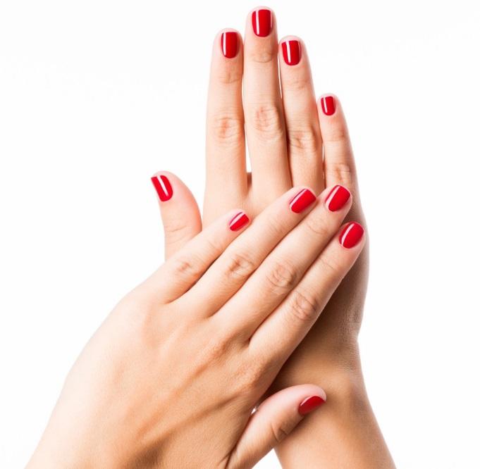 Des mains avec du vernis rouge