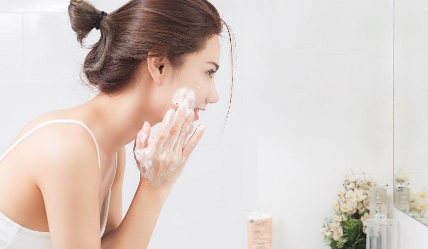 femme qui se lave le visage avec un savon doux